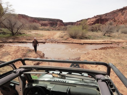 Our guide, Delbert, surveying a river crossing to make sure it's passable. (The water went up to the grille.)