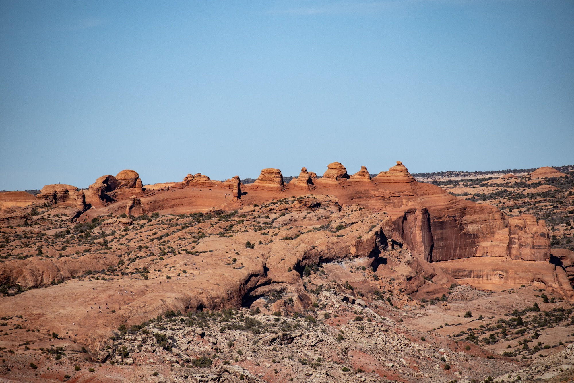 This is a unique view of the famous Delicate Arch from a distance. It appears as the thin fin of rock just left of center here.